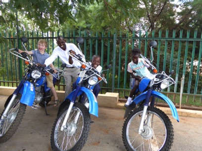 The three kids try out the Riders for Health motorcycles that Gordon is about tot ride across Zambia